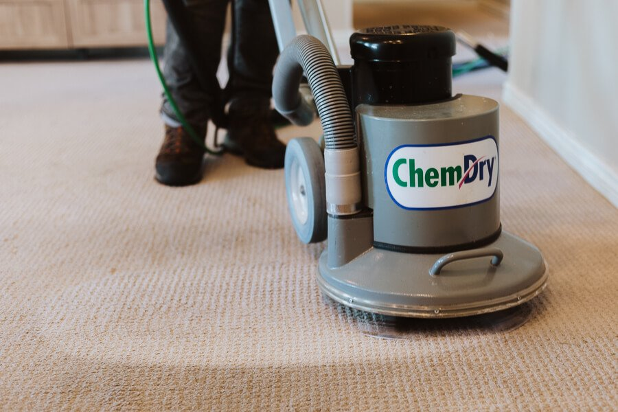 Chem-Dry technician using the hot carbonation extraction machine to clean a carpet